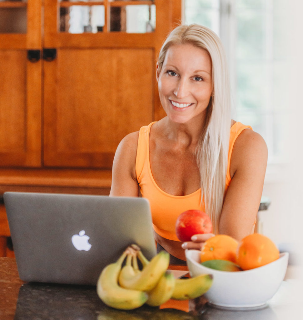 Ingrid Segev sitting on computer with fruit in her home.