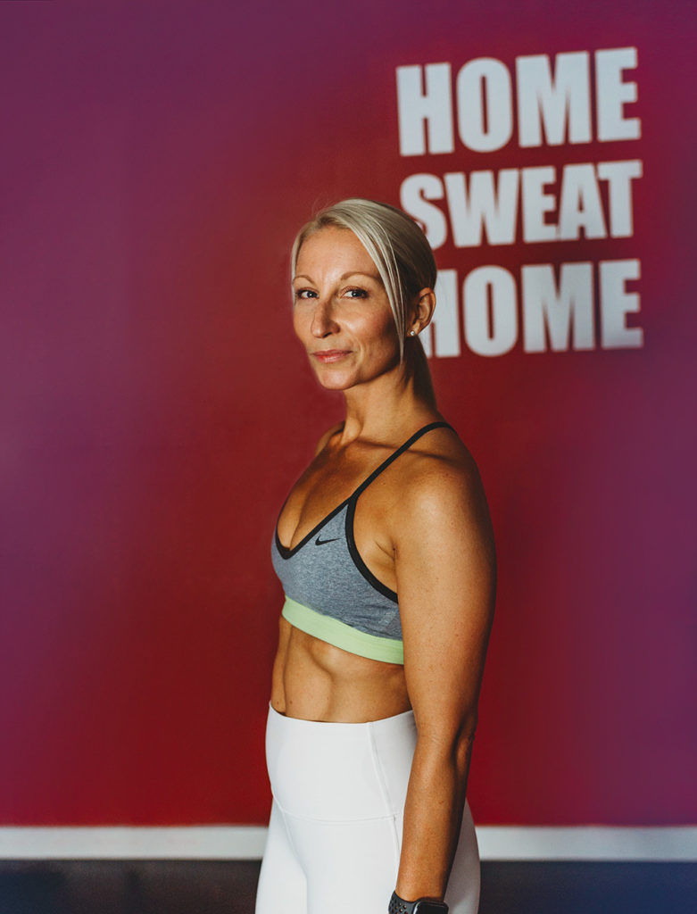 """Fitness Instructor Ingrid Segev, wearing fitness apparel, stands in front of """"Home Sweat Home"""" wall sign."""